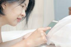 Ασιατική γυναίκα που χρησιμοποιεί το κινητό τηλέφωνο στο κρεβάτι Στοκ Εικόνες