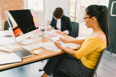 Ασιατική γυναίκα που χρησιμοποιεί το smartphone και τον υπολογιστή γραφείου στο σύγχρονο γραφείο, συνάδελφος στη γραφική εργασία  Στοκ Φωτογραφία