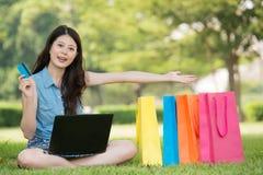 Ασιατική γυναίκα που ψωνίζει on-line με την παρουσίαση πιστωτικών καρτών στοκ φωτογραφία με δικαίωμα ελεύθερης χρήσης