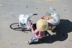 Ασιατική γυναίκα που ωθεί ένα ποδήλατο με τον εξοπλισμό μαγείρων στοκ εικόνες