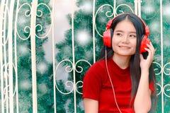 Ασιατική γυναίκα στα κόκκινα ακουστικά που απολαμβάνει τη μουσική στοκ εικόνες