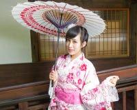 Ασιατική γυναίκα στην ομπρέλα εκμετάλλευσης κιμονό Στοκ Εικόνες
