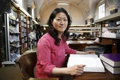 Ασιατική γυναίκα στη βιβλιοθήκη Στοκ Εικόνες