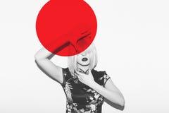 Ασιατική γυναίκα στη δορά περουκών από τον καυτό κόκκινο ήλιο Όμορφα ιαπωνικά ενδύματα ανθών sakura γκείσων ενάντια στο κόκκινο σ Στοκ εικόνες με δικαίωμα ελεύθερης χρήσης