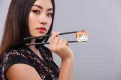 Ασιατική γυναίκα στο ιαπωνικό kimano με τα σούσια και τους ρόλους σε ένα γκρίζο υπόβαθρο διάστημα αντιγράφων Στοκ Εικόνες