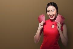 Ασιατική γυναίκα στο angpao εκμετάλλευσης φορεμάτων cheongsam Στοκ Εικόνες