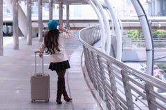 Ασιατική γυναίκα ταξιδιού που φορά το παλτό πουλόβερ, μπλε καπέλο νημάτων με το lugg Στοκ φωτογραφίες με δικαίωμα ελεύθερης χρήσης