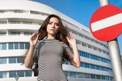 Ασιατική γυναίκα Brunette που φορά το ριγωτό φόρεμα που στέκεται μπροστά από το άσπρο κτήριο στην πόλη με το οδικό σημάδι στάσεων Στοκ Εικόνες