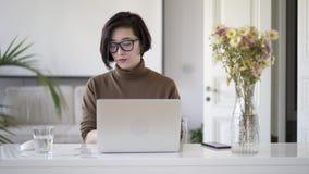 Ασιατική γυναίκα eyeglasses που λειτουργούν με το lap-top στο άσπρο Υπουργείο Εσωτερικών απόθεμα βίντεο
