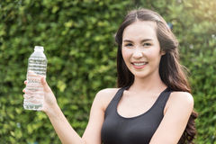 Ασιατική γυναίκα sportswear στο μπουκάλι νερό εκμετάλλευσης στη φυσική ΤΣΕ στοκ εικόνες με δικαίωμα ελεύθερης χρήσης