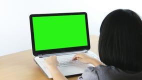 Ασιατική δακτυλογράφηση κοριτσιών σε ένα lap-top, πράσινη οθόνη απόθεμα βίντεο