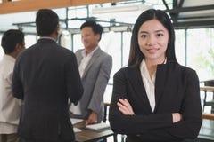 Ασιατική επιχειρηματίας με τα διπλωμένα χέρια που χαμογελά στη κάμερα εμπιστευτείτε Στοκ Φωτογραφία
