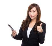 Ασιατική επιχειρηματίας με το τηλέφωνο και τον αντίχειρα κυττάρων επάνω Στοκ φωτογραφία με δικαίωμα ελεύθερης χρήσης
