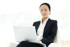 Ασιατική επιχειρηματίας που χρησιμοποιεί το lap-top στα γόνατα Στοκ Εικόνα