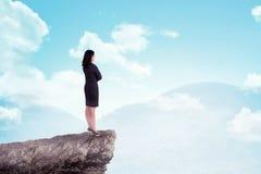Ασιατική επιχειρησιακή γυναίκα που στέκεται πάνω από το βουνό στοκ εικόνα