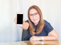 Ασιατική επιχειρησιακή γυναίκα που χαμογελά και που κρατά την έξυπνη τηλεφωνική συσκευή κενή τηλεφωνική οθόνη έξυπν& Έννοια επιχε Στοκ φωτογραφία με δικαίωμα ελεύθερης χρήσης