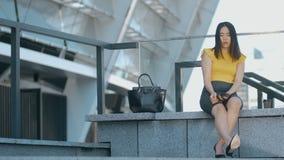 Ασιατική επιχειρησιακή γυναίκα σχετικά με τα πονώντας πόδια απόθεμα βίντεο