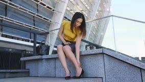 Ασιατική επιχειρησιακή κυρία που βγάζει τα τακούνια των κουρασμένων ποδιών απόθεμα βίντεο