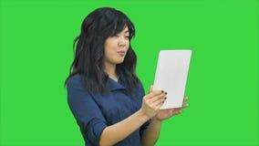 Ασιατική επιχειρησιακή κυρία που κουβεντιάζει χρησιμοποιώντας μια ταμπλέτα σε μια πράσινη οθόνη, κλειδί χρώματος φιλμ μικρού μήκους