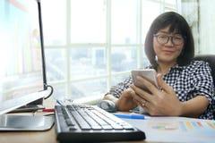 Ασιατική εργαζόμενη γυναίκα που κοιτάζει στην έξυπνη τηλεφωνική και χαμόγελου ευτυχία Στοκ εικόνες με δικαίωμα ελεύθερης χρήσης