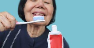 Ασιατική ηλικιωμένη γυναίκα που δοκιμάζει την οδοντόβουρτσα χρήσης, δόνηση χεριών Οδοντική υγεία στοκ φωτογραφία