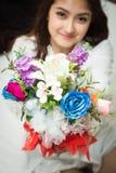 Ασιατική καυκάσια δίνοντας ανθοδέσμη των ζωηρόχρωμων λουλουδιών Στοκ Φωτογραφίες