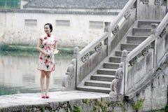 Ασιατική κινεζική γυναίκα στην παραδοσιακή στάση cheongsam σε μια αρχαία γέφυρα Στοκ Εικόνες