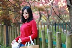 Ασιατική κινεζική όμορφη στάση χαμόγελου γυναικών από τον ξύλινο φράκτη στη φύση την άνοιξη υπαίθρια Στοκ φωτογραφία με δικαίωμα ελεύθερης χρήσης