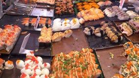 Ασιατική κουζίνα, έννοια τροφίμων κλείστε τα χέρια με τις λαβίδες επιλέγουν τα σούσια στην αγορά νύχτας στην οδό φιλμ μικρού μήκους