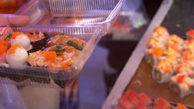 Ασιατική κουζίνα, έννοια τροφίμων κλείστε τα χέρια με τις λαβίδες επιλέγουν τα σούσια στην αγορά νύχτας στην οδό απόθεμα βίντεο