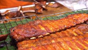 Ασιατική κουζίνα, έννοια τροφίμων κλείστε BBQ πλευρά χοιρινού κρέατος στο μετρητή στην αγορά νύχτας στην οδό φιλμ μικρού μήκους