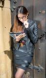 Ασιατική κυρία με τα γυαλιά και ταμπλέτα που φαίνεται στοχαστική στην πόλη Στοκ Εικόνα