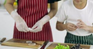 Ασιατική μητέρα και ο γιος της που κατασκευάζουν το χάμπουργκερ μαζί στην κουζίνα απόθεμα βίντεο