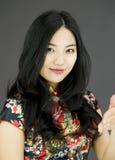 Ασιατική νέα γυναίκα που δίνει το χέρι για τη χειραψία στο χρωματισμένο υπόβαθρο Στοκ Εικόνες