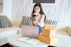 Ασιατική νέα γυναίκα που χρησιμοποιεί το smartphone που ελέγχει το προϊόν διαταγής on-line στοκ εικόνες