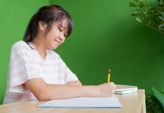 Ασιατική νέα εργασία γραψίματος κοριτσιών εφήβων στην ετικέττα σχολικών βιβλιοθηκών Στοκ εικόνα με δικαίωμα ελεύθερης χρήσης