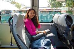 Ασιατική νέα εύθυμη γυναίκα που ταξιδεύει με το λεωφορείο στοκ εικόνες με δικαίωμα ελεύθερης χρήσης
