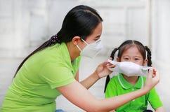 Ασιατική νέα μητέρα που φορά την προστατευτική μάσκα για την κόρη της ενώ εξωτερικό ενάντια στον ΠΡΩΘΥΠΟΥΡΓΟ 2 r στοκ φωτογραφία με δικαίωμα ελεύθερης χρήσης