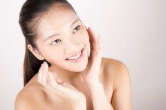 Ασιατική νέα όμορφη γυναίκα με την άψογη χροιά που χαμογελά και σχετικά με το πρόσωπο στοκ εικόνες
