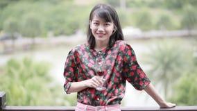 Ασιατική νεώτερη γυναίκα με το tothy πρόσωπο ευτυχίας προσώπου χαμόγελου γυαλιού κρασιού φιλμ μικρού μήκους