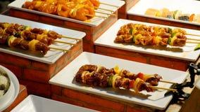 ασιατική οδός τροφίμων Τελειωμένος shish kebabs σε ένα ξύλινο οβελίδιο με τα λαχανικά στο μετρητή απόθεμα βίντεο