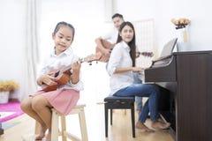 Ασιατική οικογένεια, κόρη που παίζει ukulele, κιθάρα παιχνιδιού πατέρων, σκώρος Στοκ Εικόνα