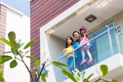 Ασιατική οικογένεια με τη στάση παιδιών στο εγχώριο μπαλκόνι στοκ φωτογραφίες