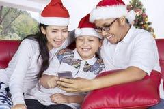 Ασιατική οικογένεια που χρησιμοποιεί ένα smartphone κοντά στο χριστουγεννιάτικο δέντρο στοκ εικόνες