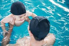 Ασιατική πισίνα μαθημάτων πατέρων και μωρών στο νερό στοκ φωτογραφία με δικαίωμα ελεύθερης χρήσης
