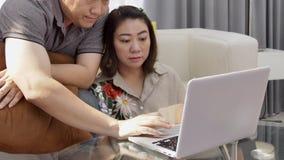 Ασιατική προσοχή ανδρών και γυναικών στο φορητό προσωπικό υπολογιστή με το πρόσωπο χαμόγελου απόθεμα βίντεο