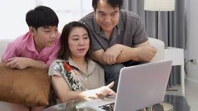 Ασιατική προσοχή πατέρων και γιων μητέρων στο φορητό προσωπικό υπολογιστή με το πρόσωπο χαμόγελου απόθεμα βίντεο