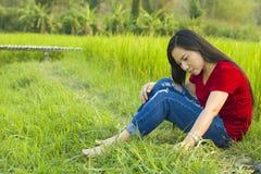 Ασιατική συνεδρίαση κοριτσιών εφήβων στον τομέα ρυζιού που σκέφτεται και που χαμογελά που υπενθυμίζεται ευτυχώς τη μεγάλη ιστορία στοκ εικόνα