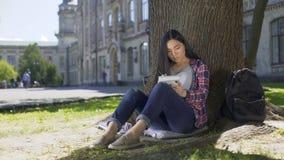 Ασιατική συνεδρίαση κοριτσιών κάτω από το δέντρο, που γράφει γρήγορα στο σημειωματάριο, έμπνευση, ποίηση απόθεμα βίντεο