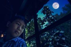 Ασιατική συνεδρίαση παιδιών κοντά στο παράθυρο και κοίταγμα κατά μέρος αισθαμένος στοκ φωτογραφίες με δικαίωμα ελεύθερης χρήσης